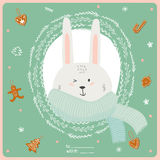 Merry Christmas and Happy New 2016 Year Card. With Happy Smiling Xmas Bunny in knittet scarf in a circle wreathe of brunches on Green Background. Greeting Stock Photos