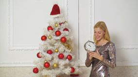 Merry Christmas and Happy New Year. Charming blonde girl is standing near Christmas tree with clock at home, smiling and. Looking at camera. White background stock video