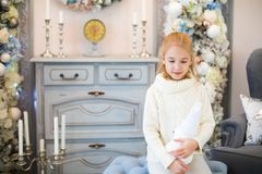Merry Christmas and Happy New Year! Charming little blonde girl in white warm sweater with toy bear sitting on the blue armchair n. Ear Christmas tree royalty free stock photography