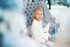 Merry Christmas and Happy New Year! Charming little blonde girl in white warm sweater with toy bear sitting on the blue armchair n. Ear Christmas tree royalty free stock photos