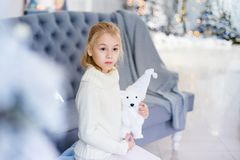 Merry Christmas and Happy New Year! Charming little blonde girl in white warm sweater with toy bear sitting on the blue armchair n. Ear Christmas tree royalty free stock image