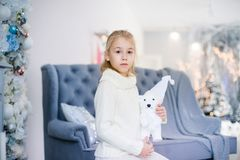 Merry Christmas and Happy New Year! Charming little blonde girl in white warm sweater with toy bear sitting on the blue armchair n. Ear Christmas tree stock photography