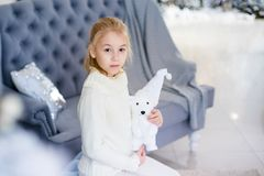 Merry Christmas and Happy New Year! Charming little blonde girl in white warm sweater with toy bear sitting on the blue armchair n. Ear Christmas tree stock photos