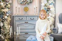 Merry Christmas and Happy New Year! Charming little blonde girl in white warm sweater with toy bear sitting on the blue armchair n. Ear Christmas tree royalty free stock images