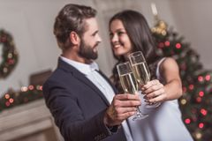 Couple celebrating New Year. Merry Christmas and Happy New Year! Cheerful and elegant couple is clinking glasses of champagne together, looking at each other and Royalty Free Stock Photo