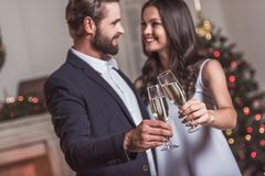 Couple celebrating New Year. Merry Christmas and Happy New Year! Cheerful and elegant couple is clinking glasses of champagne together, looking at each other and Stock Photography