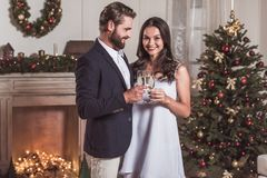Couple celebrating New Year. Merry Christmas and Happy New Year! Cheerful and elegant couple is clinking glasses of champagne together and smiling while Stock Images