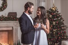 Couple celebrating New Year. Merry Christmas and Happy New Year! Cheerful and elegant couple is holding glasses of champagne, looking at each other and smiling Royalty Free Stock Photo