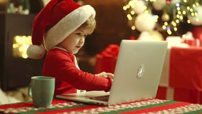 Merry Christmas and Happy new year. Christmas kids with laptot, computer. Home Christmas atmosphere. Happy cute child in stock video footage