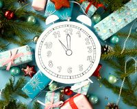Merry Christmas and happy new year. Clock, cut out of paper, surrounded by fir-tree branches and gifts. On blue background Stock Photos