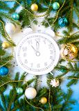Merry Christmas and happy new year. Clock, cut out of paper, surrounded by fir-tree branches and gifts. On blue background Stock Photography