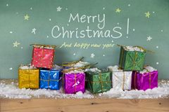 Merry christmas Happy new year. Colorful gift box. On snow wooden floorand and scene green board background space leave blank for writing greetings and Have Royalty Free Stock Image