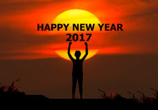 Merry christmas and happy new year 2017 concep. T. Silhouette of a businessman holding his hand to the happy new year 2017 behind the sun Royalty Free Stock Photos