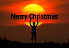 Merry christmas and happy new year 2017 concep. T. Silhouette of a businessman holding his hand to the merry christmas behind the sun Royalty Free Stock Photos