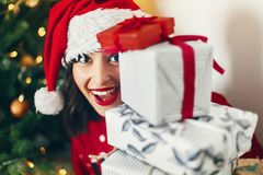 Merry christmas and happy new year concept. happy stylish woman. In santa hat holding many gift boxes with ribbon at christmas tree. space for text. seasonal Stock Photography