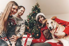 Merry christmas and happy new year concept. stylish hipster fami. Ly in festive sweaters exchanging gifts at christmas tree lights. happy holidays. funny Royalty Free Stock Image