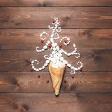 Merry Christmas and Happy New Year creative background. Magical white Christmas tree in wafer cone on a background of the brown planks Royalty Free Stock Photos