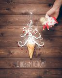 Merry Christmas and Happy New Year creative background. Magical white Christmas tree in wafer cone and angel in the hand on a background of the brown planks Stock Photos
