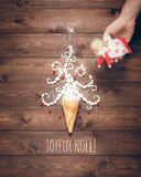 Merry Christmas and Happy New Year creative background. Magical white Christmas tree in wafer cone and angel in the hand on a background of the brown planks Royalty Free Stock Photo