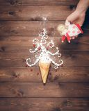 Merry Christmas and Happy New Year creative background. Magical white Christmas tree in wafer cone and angel in the hand on a background of the brown planks Royalty Free Stock Photos