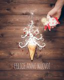Merry Christmas and Happy New Year creative background. Magical white Christmas tree in wafer cone and angel in the hand on a background of the brown planks Royalty Free Stock Image