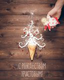 Merry Christmas and Happy New Year creative background. Magical white Christmas tree in wafer cone and angel in the hand on a background of the brown planks Stock Photo