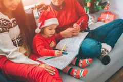 Merry Christmas and Happy New Year. Cut view of parents sitting on sofa with their child. Kid holds colouring and stock photo