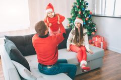 Merry Christmas and Happy New Year. Delightful picture of happy family sitting on couch. Dad plays with kid. He holds up stock photo
