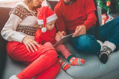 Merry Christmas and Happy New Year. Family Cut view of small girl sits between her parents. She holds tablet and points royalty free stock photography
