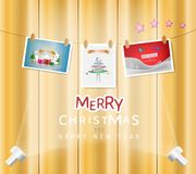 Merry Christmas and Happy New Year festival concept. Christmas postcard hanging with a rope on a wooden wall color background and text decoration. Vector Stock Photography