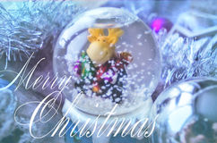 Merry Christmas and Happy New Year festive card with snow globe and Christmas-tree tinsel. Snow glass ball with moose toy. Stock Image