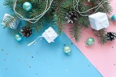 Merry Christmas and Happy New Year. Frame Christmas Card Festive with green Fir Branches and Holiday Object on pale pink and blue Background Stock Photos