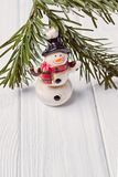 Merry Christmas and Happy New Year. Funny snowman and Christmas tree branch on white background. Free space. Merry Christmas and Happy New Year. Funny snowman Stock Photos