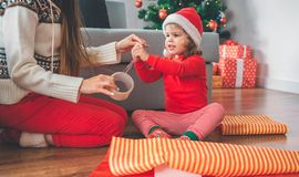 Merry Christmas and Happy New Year. Girl and young woman sit on floor. Child reaches and touches tape. Woman holds the royalty free stock image