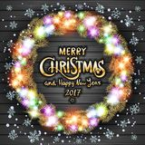 Merry Christmas and Happy New Year 2017. Glowing Christmas wreath made of led lights on the grey wooden background. Royalty Free Stock Photography