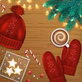 Merry Christmas and Happy New Year Greeting Background. Winter Elements fir branches, knitted red hat, mittens, cup of coffee Stock Images