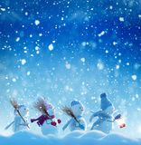 Many snowmen standing in winter Christmas landscape. Merry Christmas and happy New Year greeting card with copy-space.Many snowmen standing in winter Christmas Royalty Free Stock Image