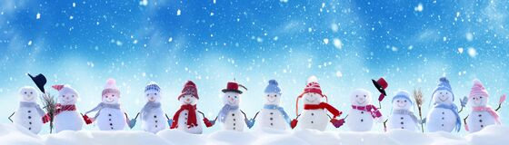 Merry Christmas and New Year greeting card with copy-space.Many snowmen standing in winter Christmas landscape.Winter