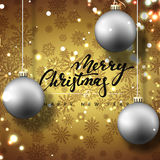 Merry Christmas and happy New Year greeting card. Golden background with Christmas balls and snowflakes. Hand Calligraphy for Xmas Holiday greeting card design Stock Photos