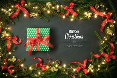 Merry Christmas and happy new year greetings in vertical top view dark blackboard with pine branches,ribbons, lights. Decorated frame and gift present box.Xmas stock image
