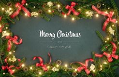 Merry Christmas and happy new year greetings in vertical top view dark blackboard with pine branches,ribbons and lights. Decorated frame.Xmas winter holiday stock image