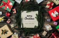 Merry Christmas and happy new year greetings in vertical top view vintage wood.Pine branches,ribbons, lights,gift. Present boxes decorated frame.Xmas winter stock image