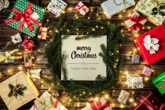 Merry Christmas and happy new year greetings in vertical top view vintage wood.Pine branches,ribbons, lights,gift. Present boxes decorated frame.Xmas winter stock photography