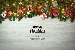 Merry Christmas and happy new year greetings in vertical top view white wood with pine branches,ribbons and lights. Decorated frame.Xmas winter holiday season stock image