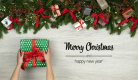 Merry Christmas and happy new year greetings in vertical top view white wood with pine branches,ribbons, lights,hands. Gift present box decorated frame.Xmas royalty free stock image