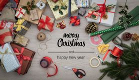 Merry Christmas and happy new year greetings in vertical top view wooden table full of christmas gifts presents, pine. And handicraft tools.Xmas winter holiday royalty free stock image