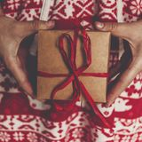 Merry christmas and happy new year. hands holding rustic present. Box with red ribbon. woman in red festive pajamas holding gift. seasonal greetings. happy Royalty Free Stock Photos