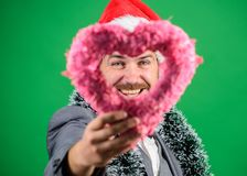 Merry christmas and happy new year. Hipster hold heart symbol of love. Bring love to family holiday. Man in love happy. Wear santa hat celebrate christmas green royalty free stock photo