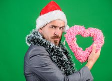 Merry christmas and happy new year. Hipster hold heart symbol of love. Bring love to family holiday. Spread love around. Man in love happy wear santa hat stock photos