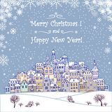 Merry Christmas and Happy New Year holiday background with inscr. Iption, urban landscape and snowfall.Merry Christmas greeting card with a small old town, trees Stock Photo